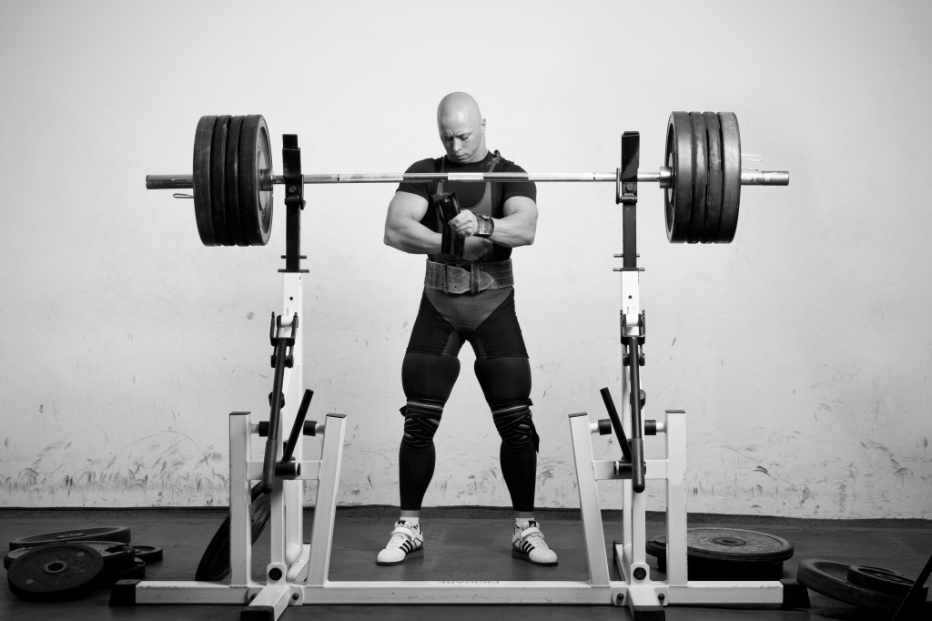 Powerlifter with strong arms preparing to lift a heavy dumbbell