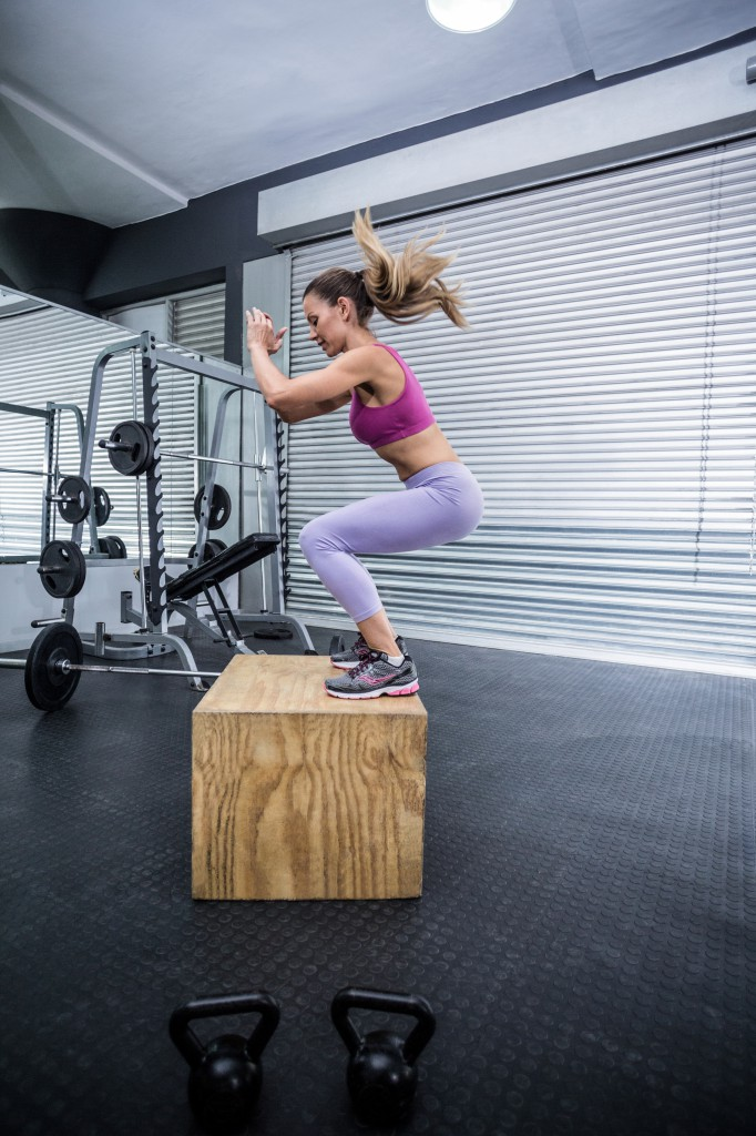 Muscular woman doing jumping squats on a wooden box