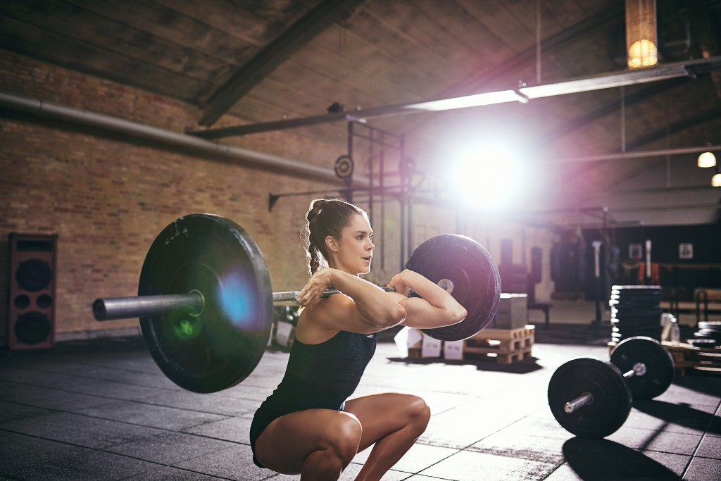 Strong woman pumping heavy barbell at gym