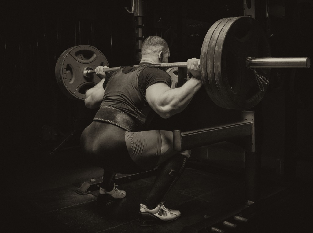 Professional athlete makes squats with a bar